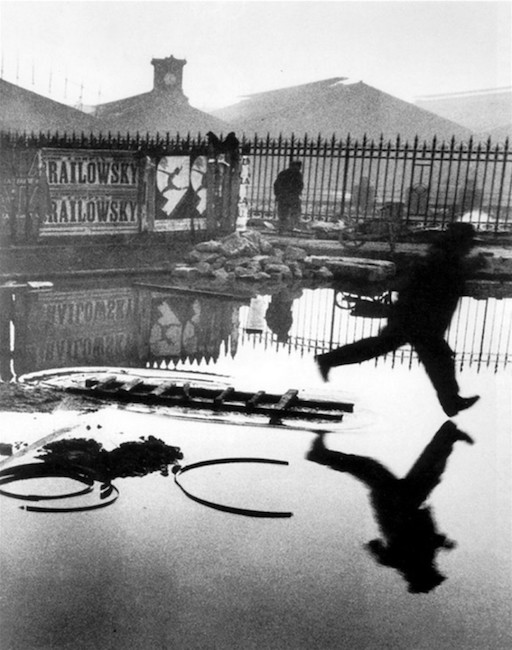 Henri Cartier-Bresson innovated street photography, bringing it to a new level in modern art. He thought of his photos as 'capturing a decisive moment,' as in 'Behind the Gare St. Lazare.'