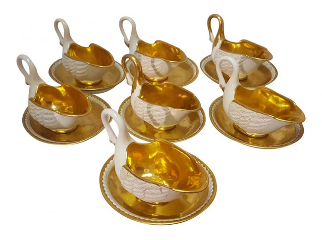 Set of seven porcelain gilded cups shaped as swans with matching saucers, circa 1810. Sold for $1,600